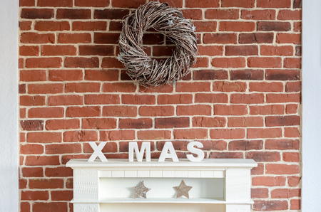 home decorated: Decorated Christmas fireplace on a brick wall in a rustic home decorated with a wreath of twigs, stocking, stars and the letters Xmas to celebrate the holiday season