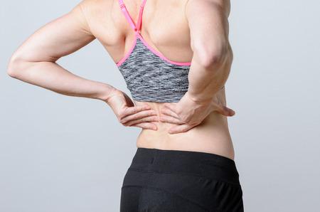 cuerpo femenino: Cierre Athletic mujer sosteniendo su dolorosa lesi�n en la espalda mientras se hace un ejercicio. Foto de archivo