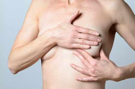 bare breast: Close up Conscious middle-aged Bare Woman Checking Some Lumps on her Breast Alone. Stock Photo