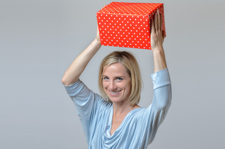 giftwrapped: Attractive blond lady with a large gift-wrapped red Christmas gift holding it over her head with a warm friendly smile, over grey Stock Photo