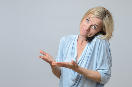 wry: Attractive blond woman standing shrugging her shoulders in ignorance, indifference or confusion with a wry smile Stock Photo