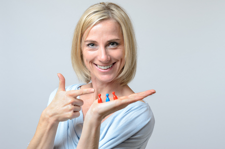 gleeful: Gleeful attractive blond woman pointing to three meeples on the palm of her hand as she displays them for the camera