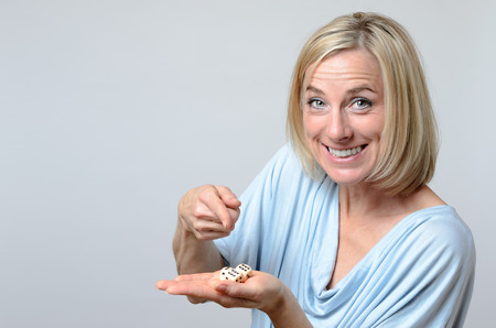 fortunate: Gleeful attractive blond woman pointing to triple six dice on the palm of her hand as she displays them for the camera