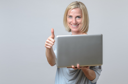 motivated: Happy motivated businesswoman giving a thumbs up gesture with a laughing smile as she is holding her laptop computer