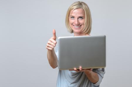 Feliz de negocios motivado dando un pulgar hacia arriba gesto con una sonrisa de risa como ella es la celebración de su ordenador portátil