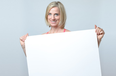 Attractive blond woman with a lovely friendly smile standing holding a blank white sign or placard in front of her chest with copy-space for your text or advertising Foto de archivo