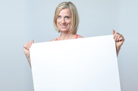 femme blonde: femme blonde Attractive avec un beau sourire permanent sympathique tenant un signe blanc blanc ou une plaque en face de sa poitrine avec copie espace pour votre texte ou de la publicit� Banque d'images