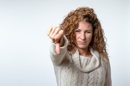 adverse: Attractive young woman giving a thumb down gesture with one hand to register her disappointment and disapproval with a serious expression