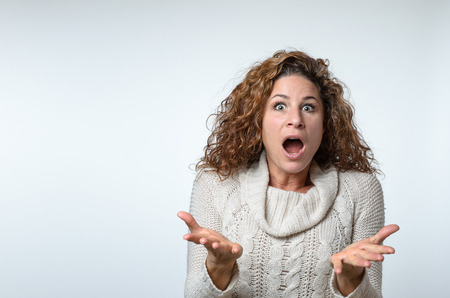 shrugs: Frustrated attractive fashionable young woman showing her ignorance and bewilderment as she shrugs her shoulders while gesturing with her hands, over grey Stock Photo