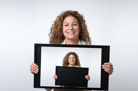 approachable: Friendly smiling attractive young woman holding up a computer or television monitor in her hands with herself on the monitor Stock Photo