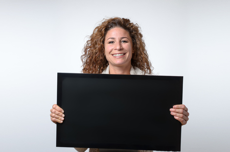 bare waist: Friendly smiling attractive young woman holding up a blank computer or television monitor in her hands with copy space for your text on the black screen