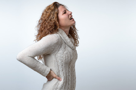 lower back pain: Young woman in a white pullover with back ache clasping her hands to her lower back as she looks up wincing in pain, side view