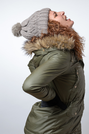 back ache: Young woman in a warm parka and knitted cap with winter back ache clasping her hands to her lower back as she looks up wincing in pain, side view