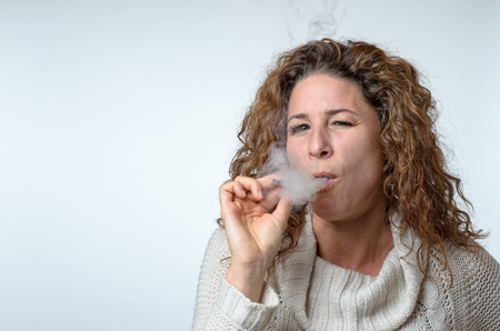 Attractive young woman puffing on a cigarette with one eye closed in enjoyment over a grey studio background