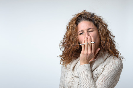 inhaling: Attractive young woman smoking three cigarettes inhaling with a look of concentration and enjoyment, head and shoulders over a light grey background Stock Photo