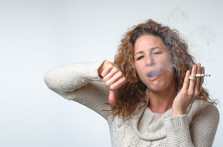 inhaling: Attractive young woman smoking three cigarettes inhaling with a look of concentration and enjoyment, giving thumb down gesture Stock Photo