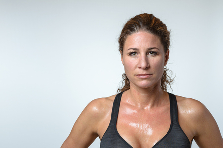 Sweaty attractive athletic fit young woman with a sheen of perspiration on her skin and lovely curly hair looking at the camera with a serious expression after a workout, head and shoulders on grey