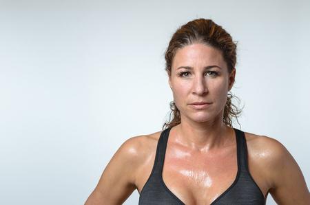 Verschwitzte attraktive sportlich fit junge Frau mit einem Glanz von Schweiß auf ihrer Haut und schönen lockigen Haaren in die Kamera mit einem ernsten Ausdruck nach dem Training, Kopf und Schultern auf grau suchen