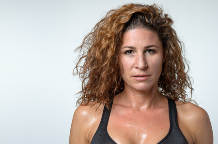 sweaty: Sweaty attractive young woman with a sheen of perspiration on her skin and lovely curly hair looking directly at the camera with a serious expression, head and shoulders on grey Stock Photo