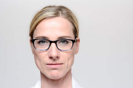 hair tied: Attractive blond woman with her hair tied neatly back wearing glasses looking directly at the camera with a serious expression, close up head shot over grey with copy space Stock Photo
