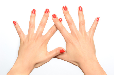 splayed: Young woman showing off her manicured nails painted with fashionable red lacquer in a close up overhead view over a white background
