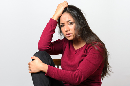 expressionless: Depressed worried young woman sitting hugging her knee looking at the camera with a serious dispirited expression Stock Photo