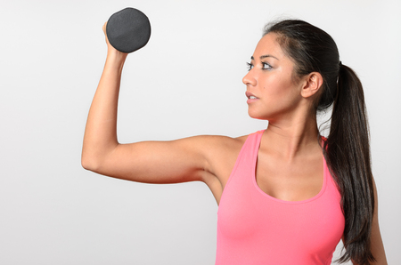 strengthen hand: Healthy fit woman working out with weights lifting a dumbbell in her hand to strengthen and tone her muscles, upper body