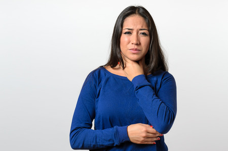 Attractive young woman with a sore throat clasping her neck with her hand and a grimace of pain as she tries to swallow