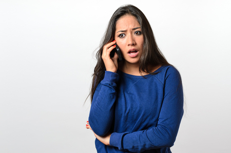 Young woman receiving bad news on her mobile listening to the call with a look of horror and consternation, upper body on white Banco de Imagens