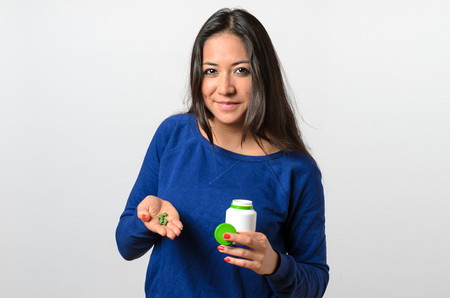 Grinning confident young woman in blue sweater holding green tablets in her palm over isolated background Banco de Imagens