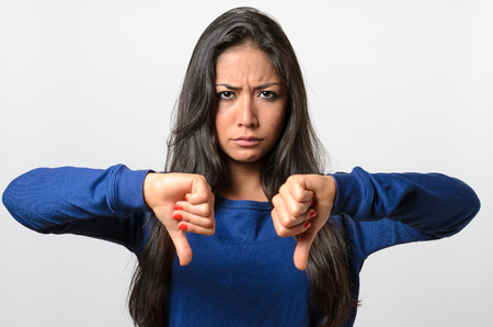 negative: Rebellious negative woman giving a thumbs down gesture with a frown to show her displeasure and register a no vote