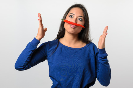 puckered lips: Goofy woman with a red hot chili pepper mustache balanced on her lip squinting and gesturing with her hands, upper body over white Stock Photo