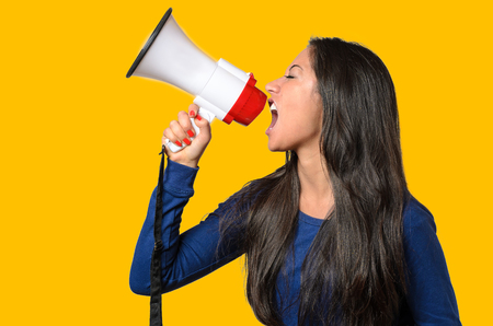 authoritative woman: Young woman shouting into a megaphone, side view on orange conceptual of a rally or protest