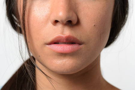 expressionless: Close up Bare Lips and Nose of a Young Woman