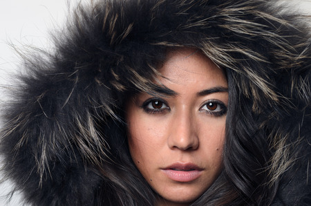 expressionless: Pretty young woman in a furry hood looking directly at the camera with a serious expression conceptual of winter fashion and beauty