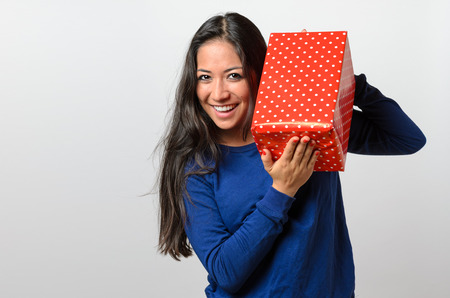 glee: Excited young woman holding a large red gift box peering over the top with a beaming smile of anticipation and glee, upper body on white