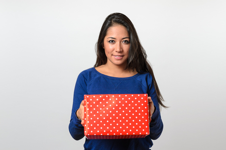 eager: Excited young woman holding a large red gift box peering over the top with a beaming smile of anticipation and glee, upper body on white