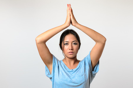 expressionless: Young woman practicing yoga raising her hands above her head with a serene serious expression as she looks at the camera, upper body on white in a wellness and healthy lifestyle concept Stock Photo