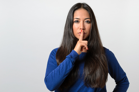 shushing: Pretty woman making a shushing gesture holding her finger to her lips as she asks for silence or to keep a secret