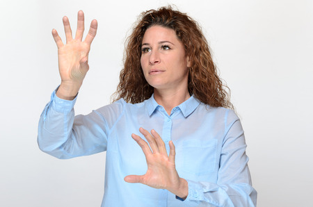 splayed: Pretty young woman using a touch screen or virtual computer interface with both hands with her fingers splayed, upper body over white Stock Photo