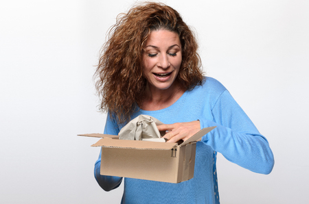 peering: Attractive young woman with lovely curly hair opening a gift box peering excitedly inside the wrapping with a smile
