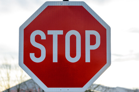 ceasing: Close up of red and white stop sign in front of obscure building outdoors