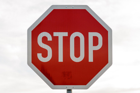 interdiction: Close up of red and white stop sign in front of obscure building outdoors