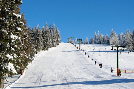 ski walking: Clear blue skies over ski resort hill with mechanical lifts and various skiers in the distance walking on the snow Stock Photo