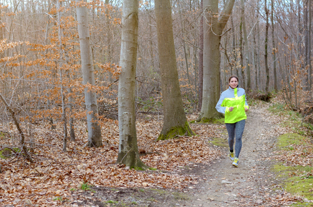 winter park: Active young woman jogging in a winter park running along a trail between trees towards the camera in a health and fitness concept