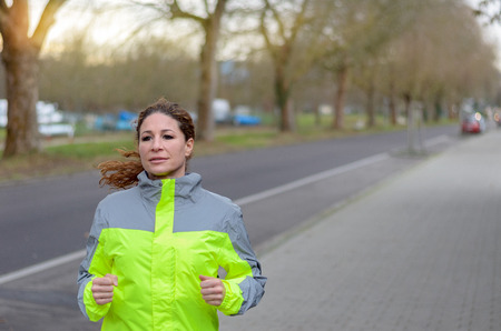 high visibility: Determined woman jogging along a street in a high visibility jacket passing in front of the camera with copy space behind in a health and fitness concept