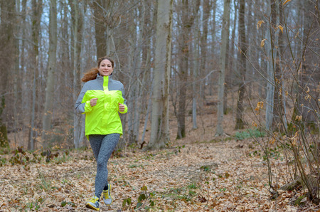 high visibility: Young woman jogging through winter woodland wearing a high visibility top for safety as she enjoys her daily workout in a healthy lifestyle concept