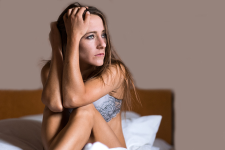 sombre: Depressed attractive young woman sitting in her bed in her underwear with her head on her hand looking to the side with a serious expression
