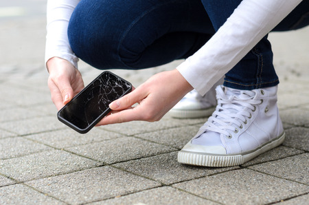 Close up view on kneeling person in jeans and shoes picking up broken phone on stone paved sidewalk outdoors