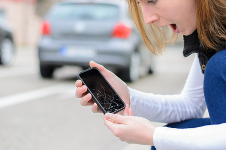 Young woman picking up her smashed mobile phone after dropping it on the cement paving of the sidewalk showing the shattered display to the camera